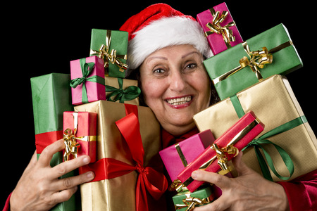 Joyful senior lady with Santa Claus cap is embracing a dozen wrapped Christmas presents. All packed in unicolored gold, red and green. Isolated on black background photo