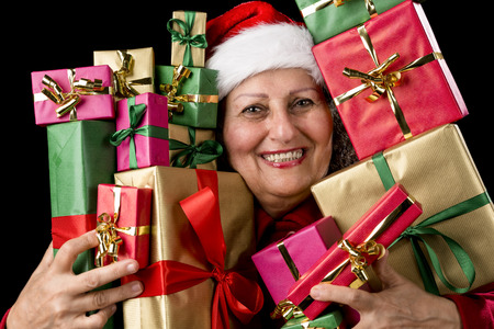 kris kringle: Cheerful elderly woman with Santa Claus hat is embosoming a host of Christmas presents Isolated on black background. Stock Photo