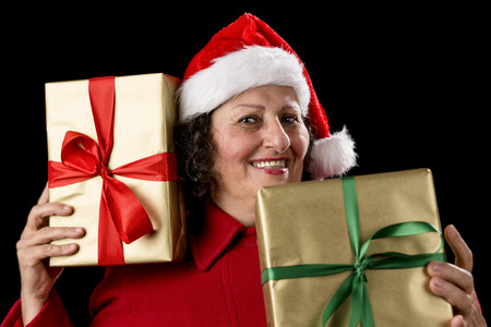 Perky senior woman is holding two gifts, one to her right cheek, the other in front of her chest Isolated on black photo