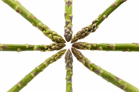 inwards: Eight green asparagus spears aligned along the vertical, horizontal and diagonal picture axes. All tips are pointing inwards and meet in the center. Vegetable isolated on white.