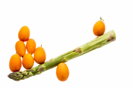 mismatch: One single green asparagus spear and eight tangerine kumquats arranged to shape a seesaw. The see-saw is imbalanced. Vegetable and fruit isolated on white. Stock Photo