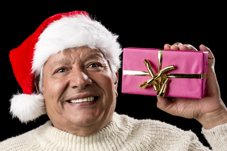 emphatic: Happy elderly gentleman with red Nicholas hat is raising a wrapped Christmas gift in his left hand. Golden bowknot. Sparkling eyes, bright teeth and white pullover. Isolated on black. Ample DOF. Stock Photo