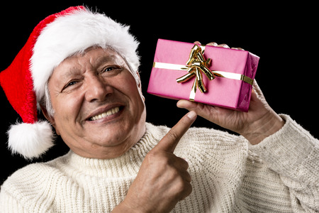 reminding: Male pensioner radiant with happiness in white pullover and red Santa Claus cap. He is reminding us of gift-giving by pointing his right index finger at a wrapped present raised up with his left hand.