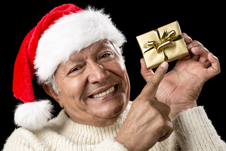 coquettish: Coquettish elderly man wearing a red Santa Claus cap and a warm, white pullover. He is pointing his right index finger at a small, golden, wrapped Christmas gift held above eye-level in his left hand.
