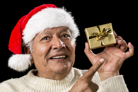 Smiling old man with challenging gaze is gesturing with his raised right index finger. He is pointing at his left hand holding a small, golden, wrapped present. Red Father Christmas cap. Ample DOF.