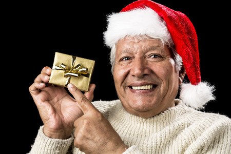 Male pensioner with a gentle smile is pointing at a small, wrapped, golden present held up in his right hand. Red Father Christmas cap and warm pullover. Isolated over black background. Ample DOF. photo