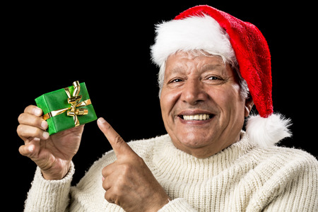 Jolly male senior pointing at small, green, wrapped gift presented in his right hand. Red Father Christmas cap, warm pullover. Present decorated with golden bowknot. Isolated over black background. photo