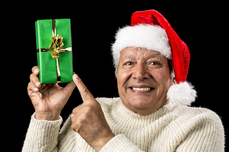 Light-hearted male senior with a red Father Christmas cap cracking a smile. He is pointing at a long, green, wrapped gift raised above eye-level in his right hand. Golden bowknot. Isolated on black. photo