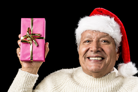 Upbeat smiling male senior lifting up an oblong present wrapped in pink and decorated with golden bowknot. Casual pullover and red pointed cap with pompon. Party mood and gift giving occasion. photo