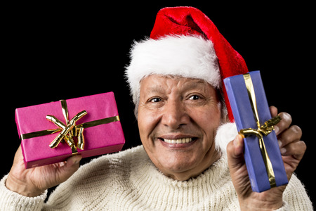 kind hearted: Gently smiling male pensioner proffering a blue and a pink wrapped present. Each with golden bow. Red Santa Claus cap and white sweater. Isolated over pitch black background. Gift giving theme. Stock Photo
