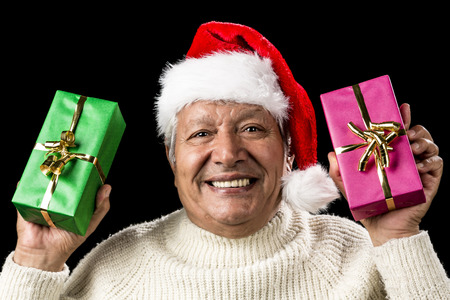 kind hearted: Cheerful and excited aged gentleman waving two wrapped presents like flags. Red Father Christmas hat. Sparkling eyes, cracking a smile. Gift-giving, festive or party theme. Isolated on black. Stock Photo