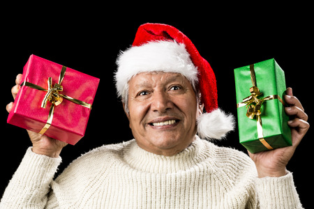 emphatic: Honorable old man with Santa Claus cap his showing a red and a green wrapped present. Emphatic gaze, coy smile, teeth showing. Gifts with golden bows. Isolated over black background. Ample DOF.
