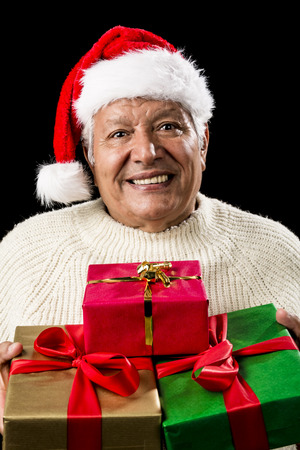 beardless: Kind male pensioner with Father Christmas hat and white sweater. Gentle smile, attentive gaze. He is offering three wrapped presents, red, green and golden. All gifts with bowknots. Isolated on black.