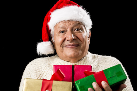 beardless: Friendly, but perplexed looking male pensioner with Santa Claus cap. He is carrying Christmas presents in front of his chest. Wrapped in green, red and gold. Isolated on black. Gift giving theme.