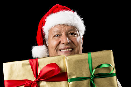beardless: Smiling male senior peeping across two foot-long gifts that cover his chest and chin. Both presents wrapped golden with green and red bows. Father Christmas hat. Gift giving theme isolated on black.