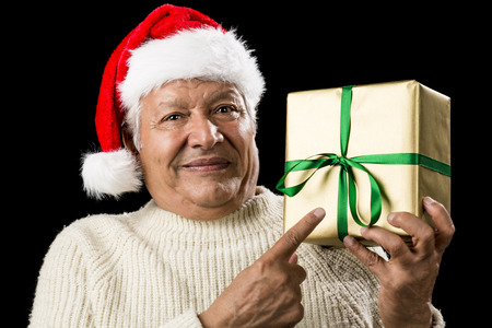 beardless: Venerable gentleman pursing his lips, while pointing at a square golden gift held in his left hand. Present is tied with a green ribbon. Red Father Christmas cap and white pullover. Isolated on black. Stock Photo