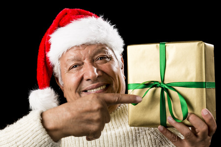 beardless: Kind old man with astute smile gesturing with his right index finger at a wrapped golden present raised to his shoulder in his left hand. Reminder for gift giving. Green bowknot. Red Santa Claus cap.