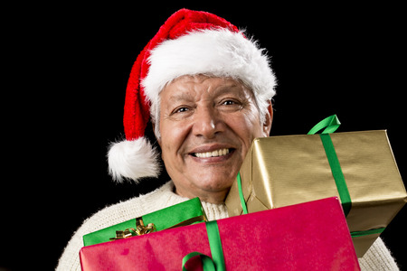 beardless: Hilarious aged gentleman carrying three Christmas gifts loaded onto his chest. Presents wrapped in plain red, green and gold. Wide, hearty smile. Santa Klaus cap. Gift giving theme isolated on black.