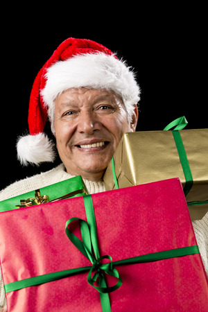 beardless: Vertical shot of merry old man carrying three differently sized gifts loaded onto his chest. Presents wrapped in gold, red and green. Kris Kringle hat. Cut-out on black. Seasonal gift giving theme. Stock Photo