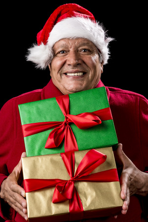 beardless: Male Senior brimming over with mirth, while handing over two foot-long presents, wrapped golden and green. Both with bowknot. Red Santa Claus cap and winter coat. Cut out on black. Gift giving theme. Stock Photo