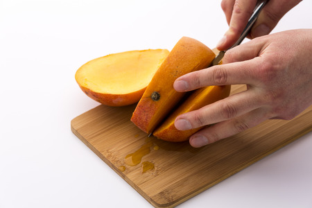 forcing: Second section through a mango does leave three equal thirds. Left fingertips positioning the fruit on a wooden board, while a right hand is forcing the blade along the oblong fruit pit. White ground. Stock Photo