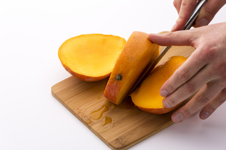 pip: Knife finishing a second cut through a ripe mango. Forcing apart a third slice from the middle slab containing the fruit pip does reveal tangerine, juicy pulp of this tropical delicacy. White ground.