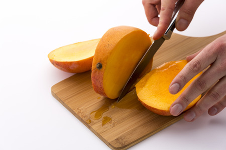 exerting: Trisecting a mango with a second cut along its oblong, flat pit. Finger tips exerting gentle pressure onto the kitchen knife used. Yellow and tangerine fruit pulp in orange skin. White background. Stock Photo
