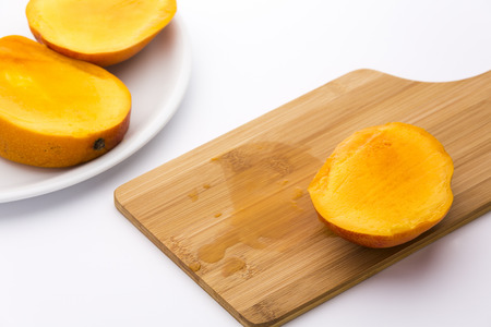 two and two thirds: Third of a ripe mango and its juice on a wooden cutting board. The remaining two thirds placed on a plate. Deep yellow fruit pulp in tangerine peel. Medium DOF. Photographed on white background.