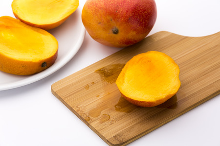 Golden yellow third of a trisected mango. Its ripe fruit flesh bedewing the wooden cutting board beneath. The remaining two thirds on a white plate next to an entire mango. White background.