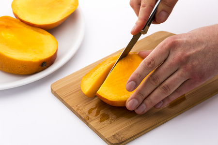 subdivided: Close up of a third of a juicy mango being subdivided into fruit chips with a first cut. The remaining two slices resting in a plain plate. Mango juice dripping onto wooden cutting board beneath.
