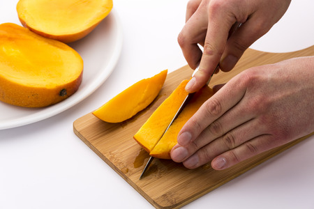 exerting: Two hands cutting the first of three equal mango slices into fruit chips. A kitchen blade is exerting a second cut through the juicy fruit pulp of the flat mango third. Close up. White background.