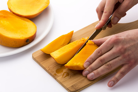 subdivided: One third of a mango being subdivided into three chips. A left hand is keeping the fruit slice in place on a wooden board, while a right hand is cutting with a kitchen knife. White background. Stock Photo