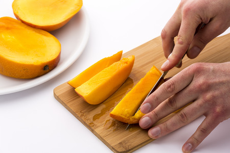 two and two thirds: One of the two outer thirds of a mango divided into three slices is being cut into four pieces. One hand is positioning the fruit chips, while the other is guiding a kitchen knife. White background.