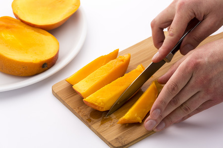 two and two thirds: Pair of hands finished subdividing a mango third into four fruit chips. Knife and cutting board bedewed with the juice of this delicious tropical fruit. Two whole mango thirds waiting on white plate. Stock Photo