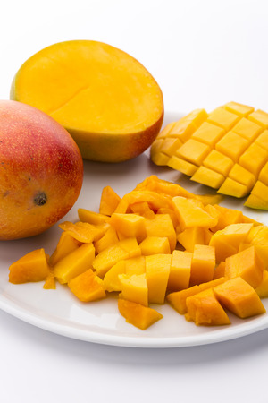 Heap of freshly cut mango pulp cubes on a plate. A mango third scored to shape dice that still are attached to the peel. A mango cross-sectioned along its pit. White background. Vertical orientation. Stock Photo