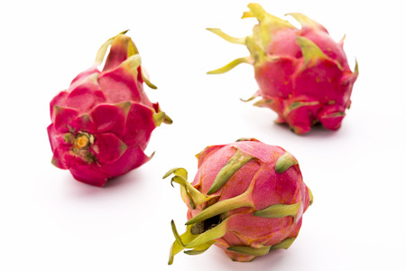 Three entire dragonfruits placed on a white kitchen surface. The leathery skin of this exotic cactus fruit is shining in vibrant pink and magenta with leaves in lush green. Also named pitaya. Imagens - 35527517