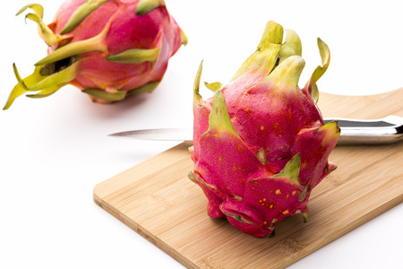 dragonfruit: Close-up of a whole dragonfruit and a kitchen knife placed on a wooden cutting board. A second entire pitaya is placed behind on the clean white table top. Lush colors. Vibrant pink and magenta.