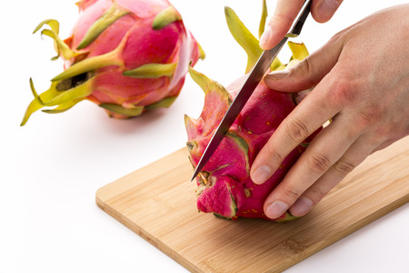 blade cut: Close-up of a kitchen knife positioned for a first cut through a dragonfruit. A chef�s left hand is placing the pitaya on a cutting board, while his right is guiding the blade. White background.