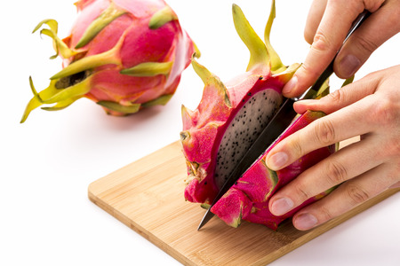 dragonfruit: Close up of a kitchen knife dividing a pitaya into two equal halves. The finger tips of a chef are guiding the blade and fixing the dragonfruit on a bamboo cutting board. White background.