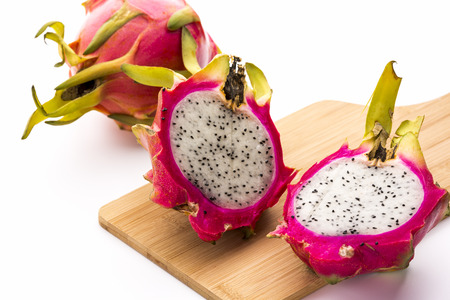 dragonfruit: Close-up of two halves of a divided dragonfruit placed on a cutting board. Juicy white pulp with tiny black seeds. The fruit flesh is surrounded by vibrant purple skin. An entire pitaya in the back.