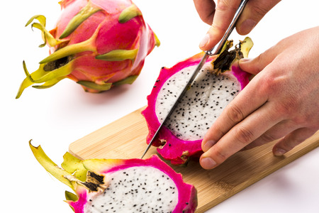 fingertips: Close-up of a chef�s hands performing a first cut through one half of a divided dragonfruit. His left is placing the pitaya on a cutting board, while his right is guiding the knife. White background. Stock Photo
