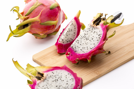 red skinned: Close-up on cut dragonfruit pieces on a wooden cutting board. The creamy white pulp of this exotic fruit is firmly embedded in its leathery skin. Colors range from pink, red and magenta to purple. Stock Photo