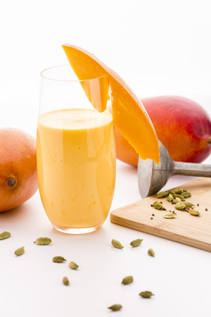 lassie: Mango milk shake in a glass decorated with a cut fruit chip. Crushed cardamon seeds on a wooden cutting board. A metal pestle and two entire mangos. Closeup. Selective focus. White background.