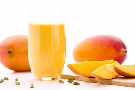 mango fruta: Primer plano de piezas de corte de mango sobre una tabla de madera. Un vaso lleno de mango lassi, semillas de cardamomo y dos mangos enteros. Enfoque selectivo. Tiro de �ngulo bajo. Fondo blanco y brillante superficie de la mesa. Foto de archivo