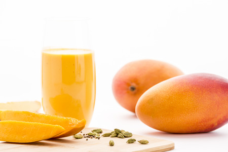 lassie: Cut mango fruit pieces and crushed cardamon on a bamboo cutting board. Key ingredients for the homemade mango yoghurt drink served in a plain drinking glass. Two whole mangoes. White background.