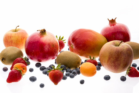 multivitamin: Wide variety of assorted whole fruit isolated on white. Ripe strawberries, blueberries, apricots, kiwi fruits, apples, pomegranates and mango. Fresh multivitamin arrangement. Closeup. Selective focus. Stock Photo