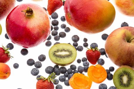 multivitamin: Half of a kiwi amidst other fruit isolated on white background. Pomegranate, mango, apple, apricot, strawberry and plenty of blueberries for a multivitamin boost. Cut-out. Close-up.