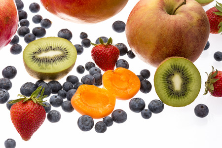 multivitamin: Close up on a halved apricot and kiwi among other fruit. Isolated over white, yet reflective, surface. Apple, strawberry, countless blueberries for a multivitamin mix. Selective focus. Macro shot. Stock Photo
