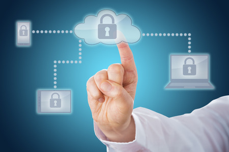 converged: Raised index finger touching a locked cloud icon linked via dotted lines to mobile and tablet devices within a network. Cell phone, tablet and laptop computer all display the lock on-screen. Close up. Stock Photo