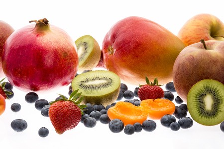 multivitamin: Exotic and nontropical fruit for a multivitamin boost. Apricot, mango, pomegranate, kiwi, apple, strawberry and blueberry. All isolated on white. Close up. Selective focus. Cutout. Low camera angle.